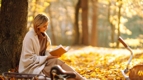 Beautiful-young-woman-sitting-on-a-fallen-autumn-leaves-in-a-park-GettyImages-1264459995.jpg
